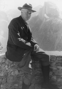 Stephen T. Mather, first Director of the National Parks Service, seated in front of Yosemite National Park's iconic Half Dome.