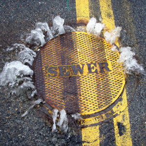 "An SSO spills out from beneath a manhole cover.  Photo: Mystic River Watershed Association, ""Sewer overflowing."""