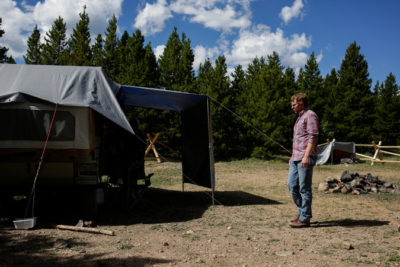 A man approaches a homeless camp at a park in Colorado.